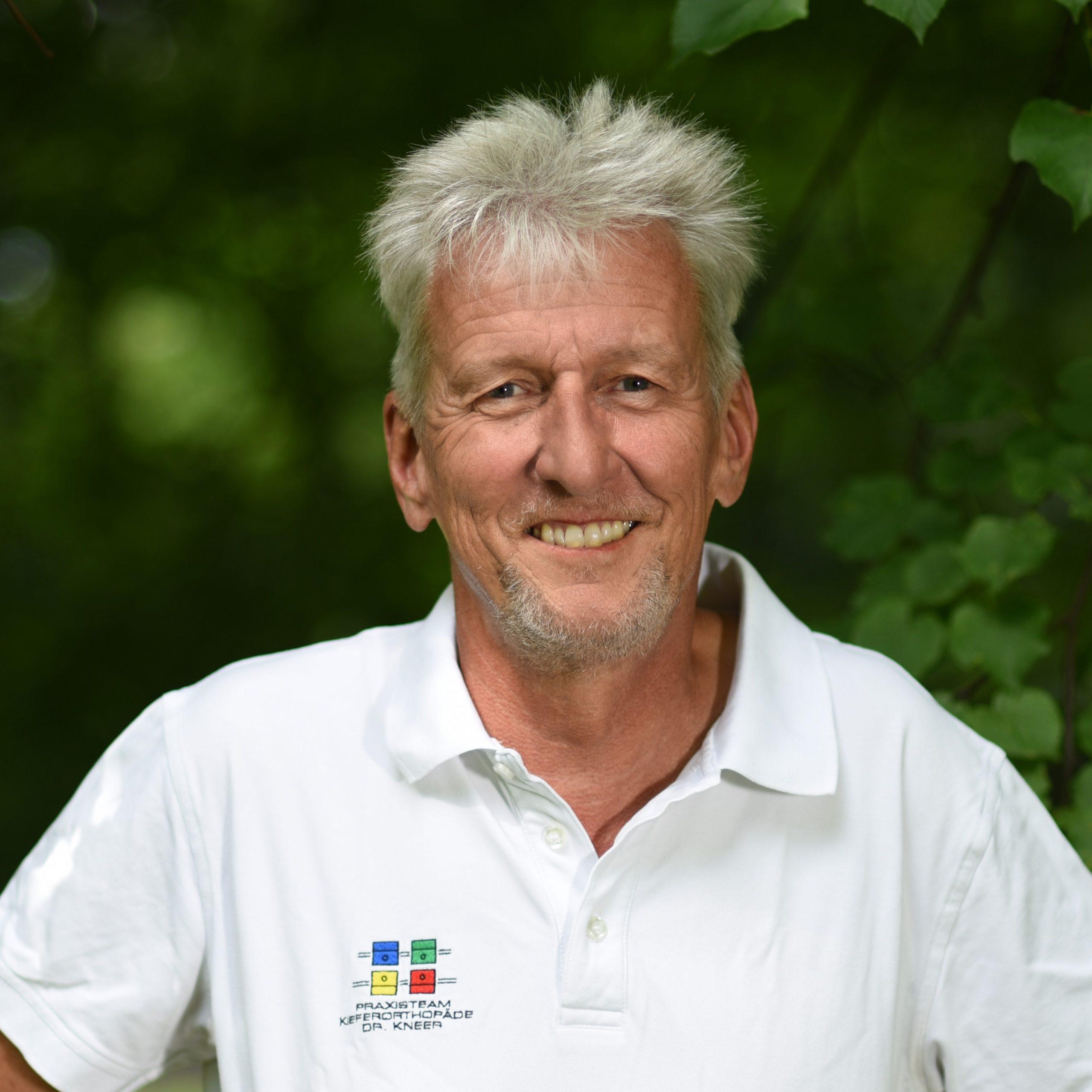 Dr. Stefan Kneer Kieferorthopäde im weißen T-Shirt